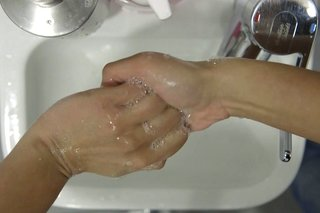 image of cleaning palms of hands over the sink